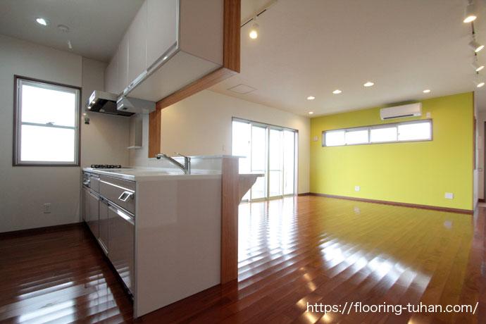 キッチン回りと黄色の壁紙が印象的なリビング