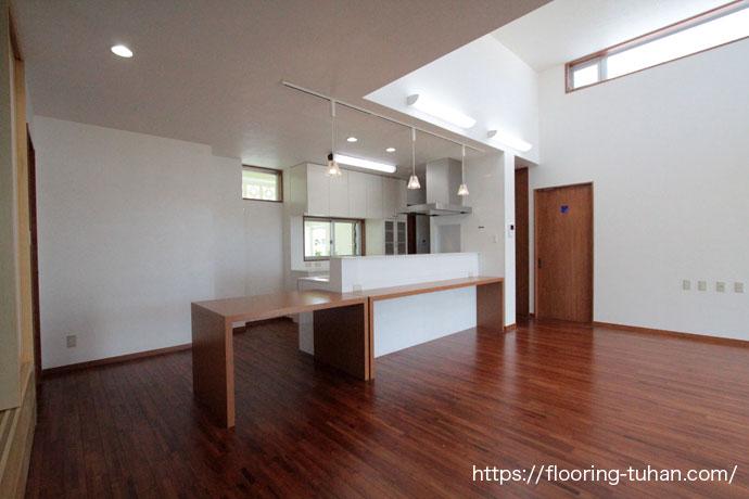 高い天井と白い壁、チーク材の色を活かして落ち着いた空間になったリビング
