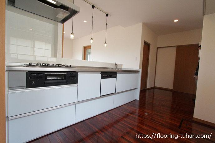 キッチンの白が映える赤褐色の色合いのメルバオ無垢フローリング